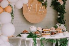 a neutral dessert table with a balloon garland with greenery and blooms, a name sign, a trestle table and greenery garlands