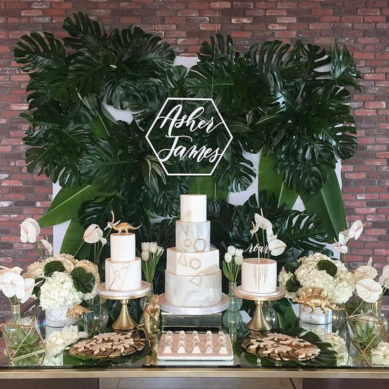 a neutral dessert table with a tropical feel, a lush tropical leaf wall, touches of gold, dinosaurs and white blooms
