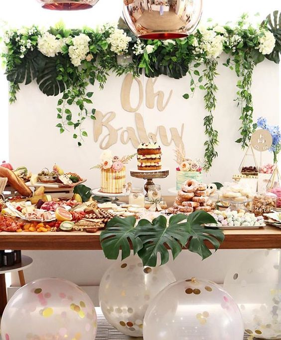 a neutral dessert table with lush greenery and white bloom garlands, large balloons with confetti, tropical leaves