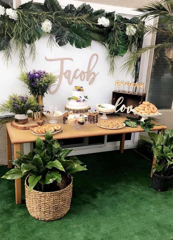 a neutral dessert table with tropical leaves and plants, with white and purple blooms and lots of sweets