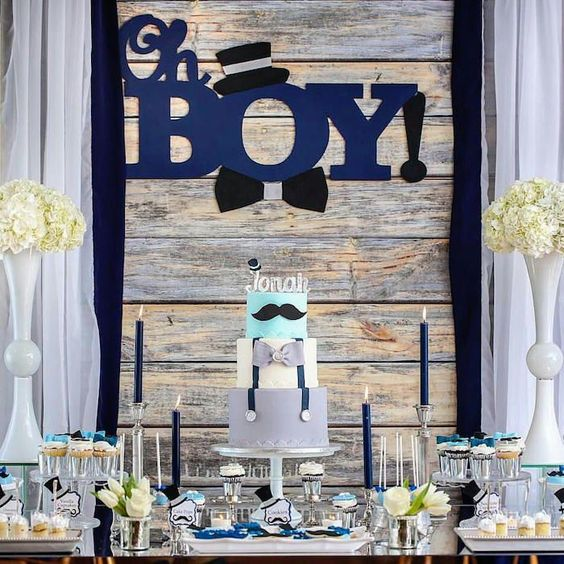 a rustic boy's baby shower dessert table with navy candles, white floral arrangements, letters on the backdrop and sweets