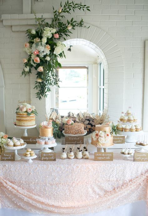a tender blush dessert table with a large scale sequin tablecloth, a lush greenery and bloom decoration and lots of desserts