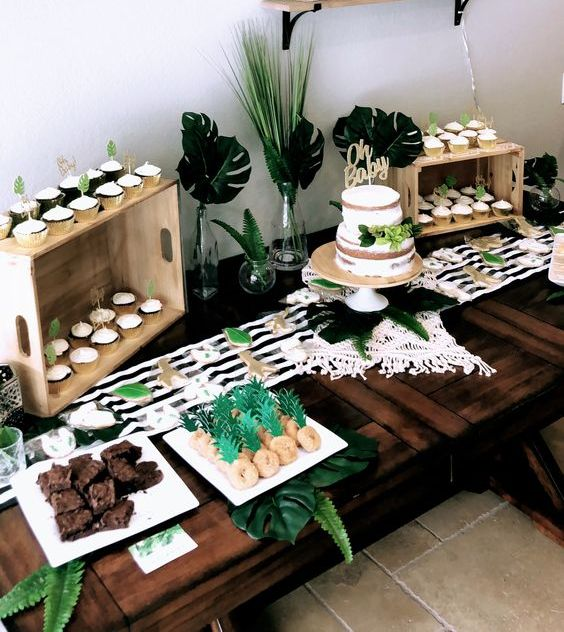 a tropical dessert table done in black and white with touches of green, with stripes, tropical leaves and delicious sweets