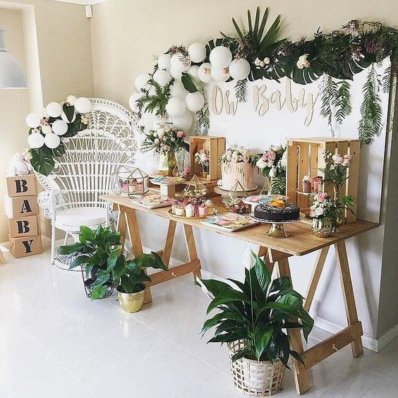 a tropical dessert table with a tropical greenery garland, white balloons, potted plants and a trestle table with crates to serve the food