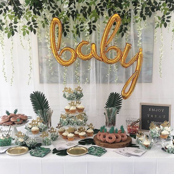 a tropical dessert table with gold calligraphy balloons, tropical greenery, a sign and lots of delicious sweets