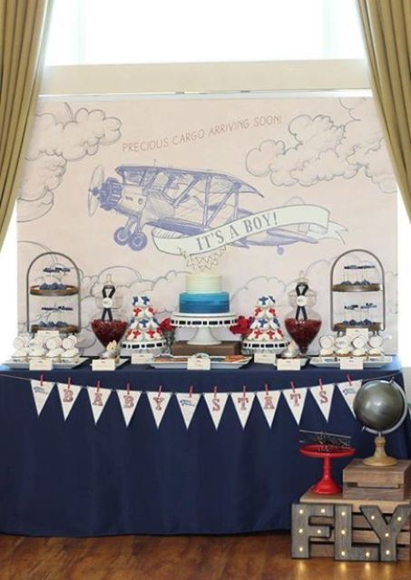 an aviation-themed dessert table with a banner, a plane backdrop, stands with sweets and cakes