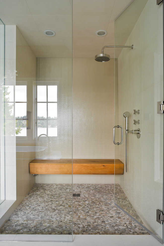 Pebble tiles on a floor mixed with white ones on walls to create this cool walk-in shower. Although a wooden bench is what makes it so cozy. (Laura Bohn Design Associates)