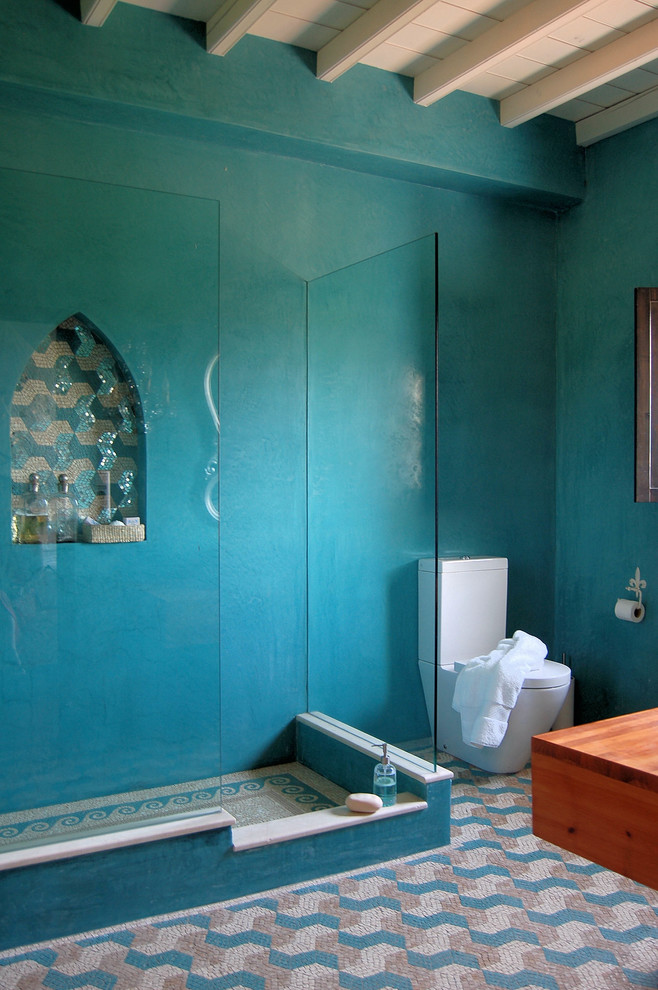 A Mediterranean bathroom with painted walls but creatively tiled flooring. (Casa Mosaica Studio)