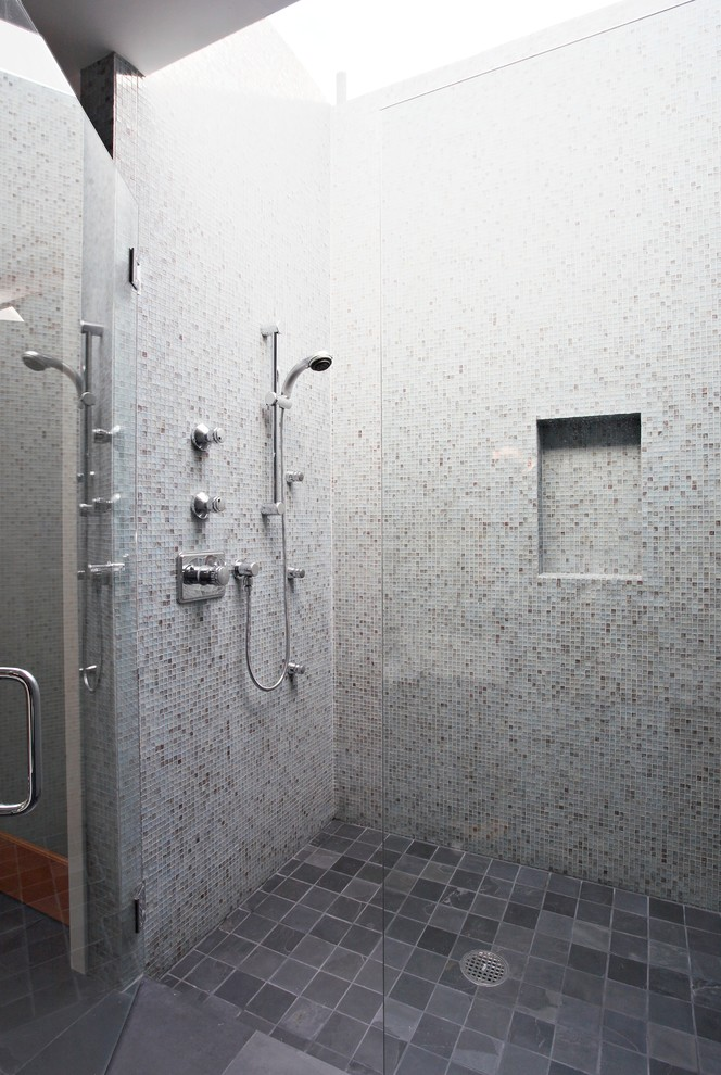 A modern walk-in shower with walls covered in mosaic tiles in different colors. (Wallace Remodeling, Inc.)