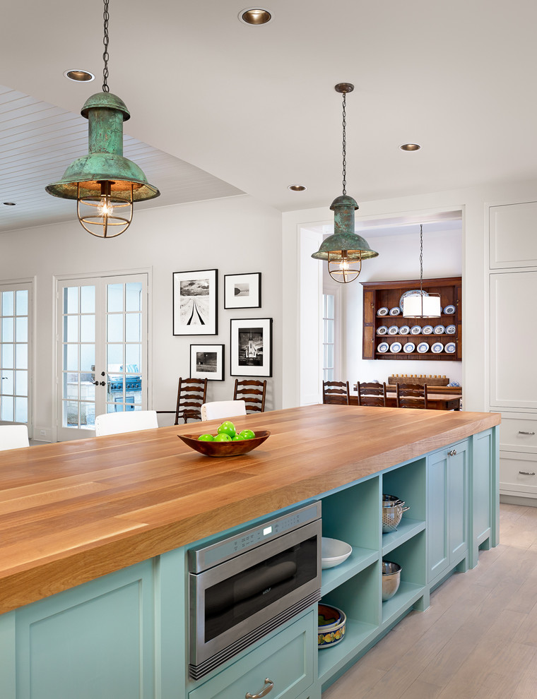 Turquoise kitchen island with a butcher countertop and a built-in microwave. (Dillon Kyle Architects (DKA))