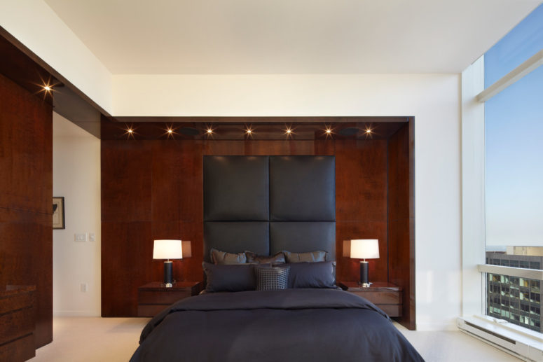 a headboard upholstered in gray fabric looks great against a dark wood accent wall (Bromley Caldari Architects PC)