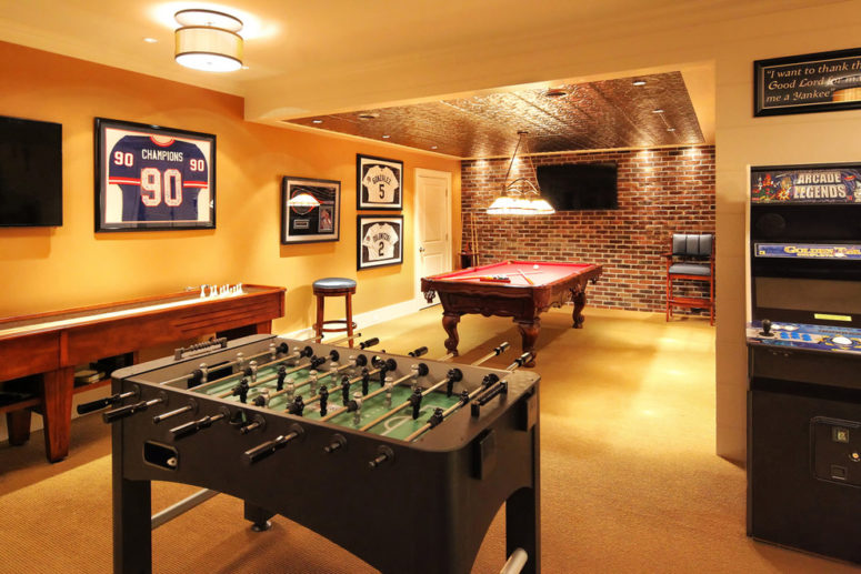 a pinball machine, a pool table and a football table are an ultimate combo for a game area (Knight Architects LLC)