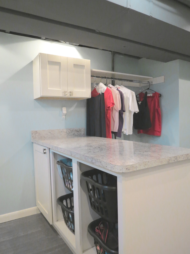 If your laundry room is in a basement provide enough storage for laundry baskets, hanging clothes and for other cleaning supplies. Countertop surface is also a must. (Woodmaster Kitchens)