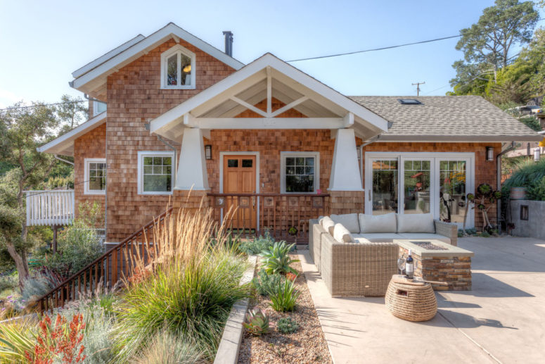 a craftsman style house with an amazing outdoor area and a porch covered with a gable roof leading to it