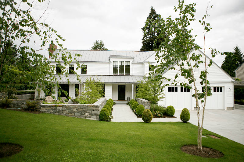 Crisp White Farmhouse Surrounded By Green Shrubs