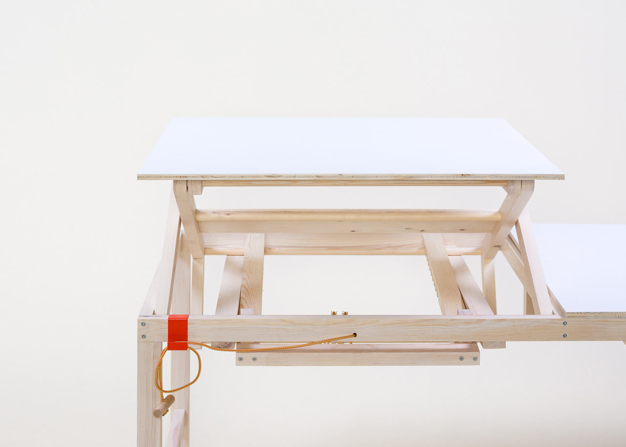 This adjus.table is made of light colored wood and can be regulated manually