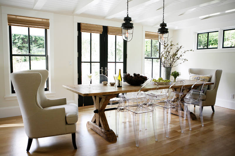 In the dining area a rustic farmhouse table is combines with transparent modern chairs