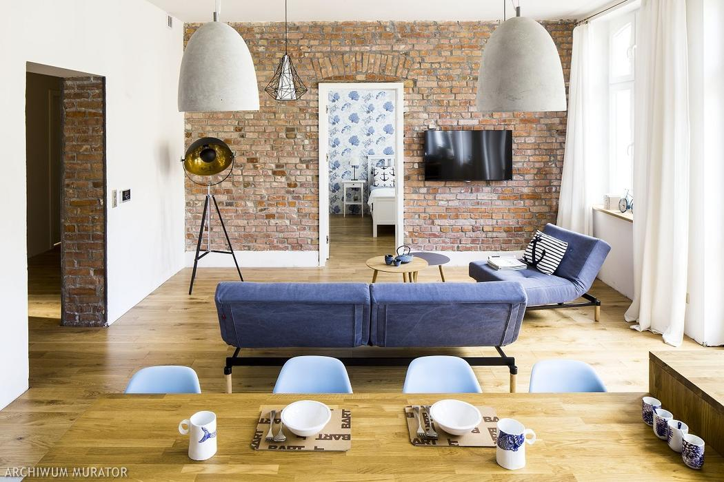 The living room part features a rough brick wall left from the previous times