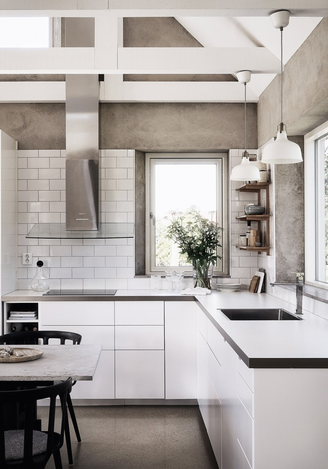 The kitchen is white and modern, concrete walls mix with white tiles and cabinets