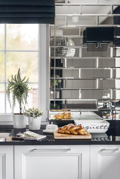 One of the walls is clad with large mirror tiles that add glam chic and make the kitchen look bigger