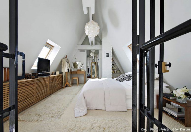 The bedroom decor was softened with the help of light-colored furniture of natural wood