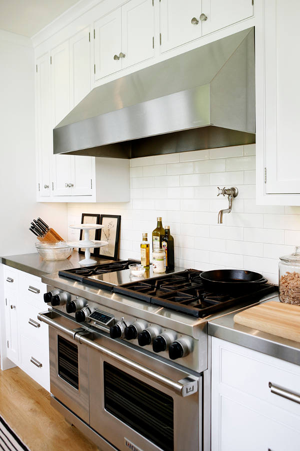 The kitchen is modern but subway tiles and wooden floros make it more traditional