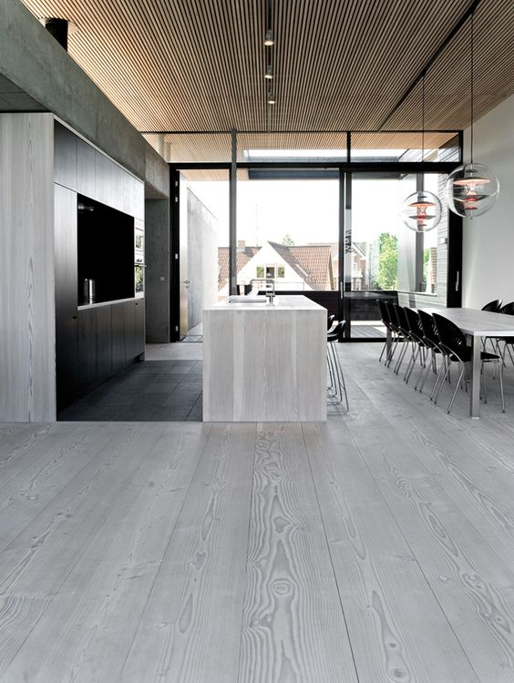 Modern Kitchen With Grey Wood Floors Going Up To The Walls And Island