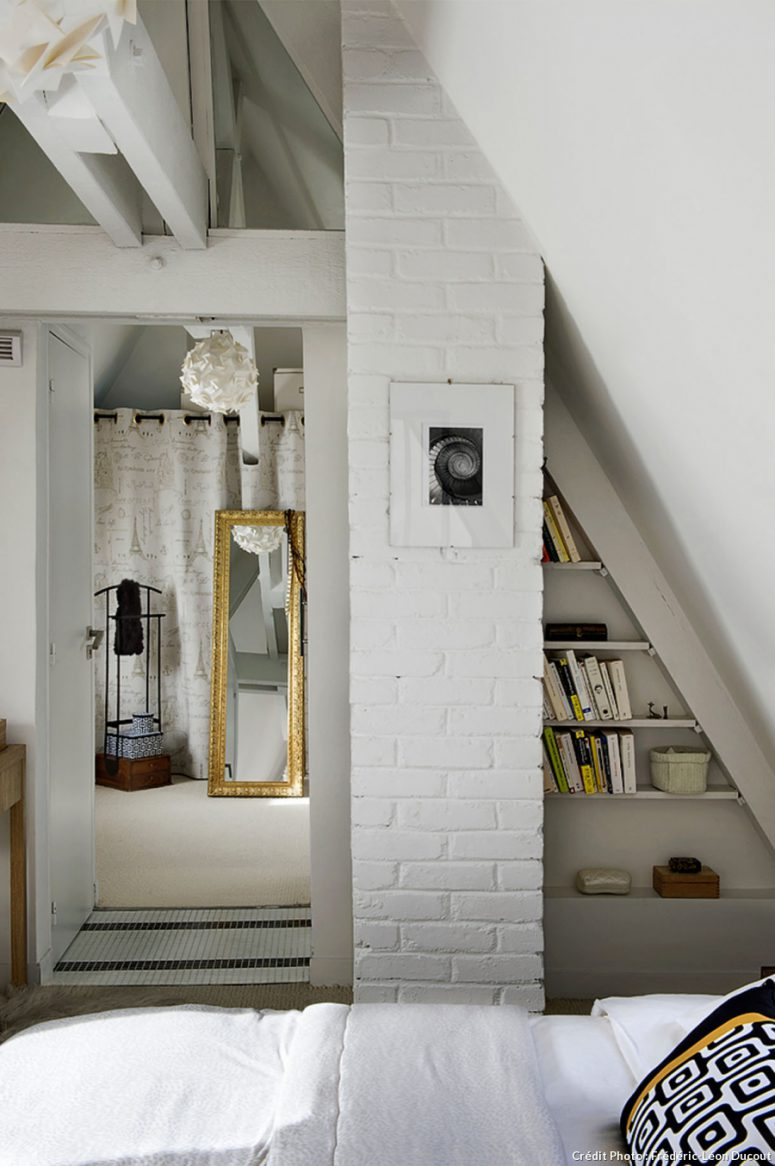 Elements of whitewashed brick clad give the bedroom a character