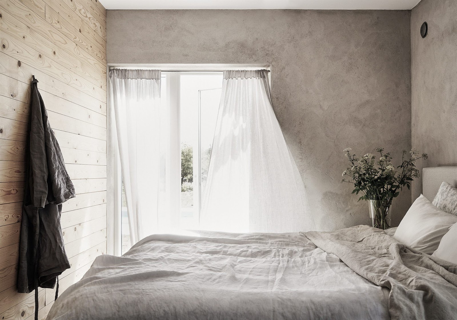 The master bedroom is decorated with concrete, fabrics give texture to the decor