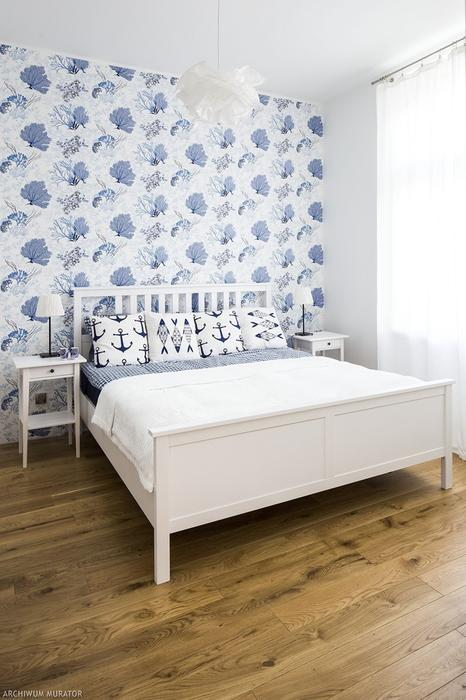 The master bedroom is decorated with white IKEA pieces and an accent wall with blue coral print