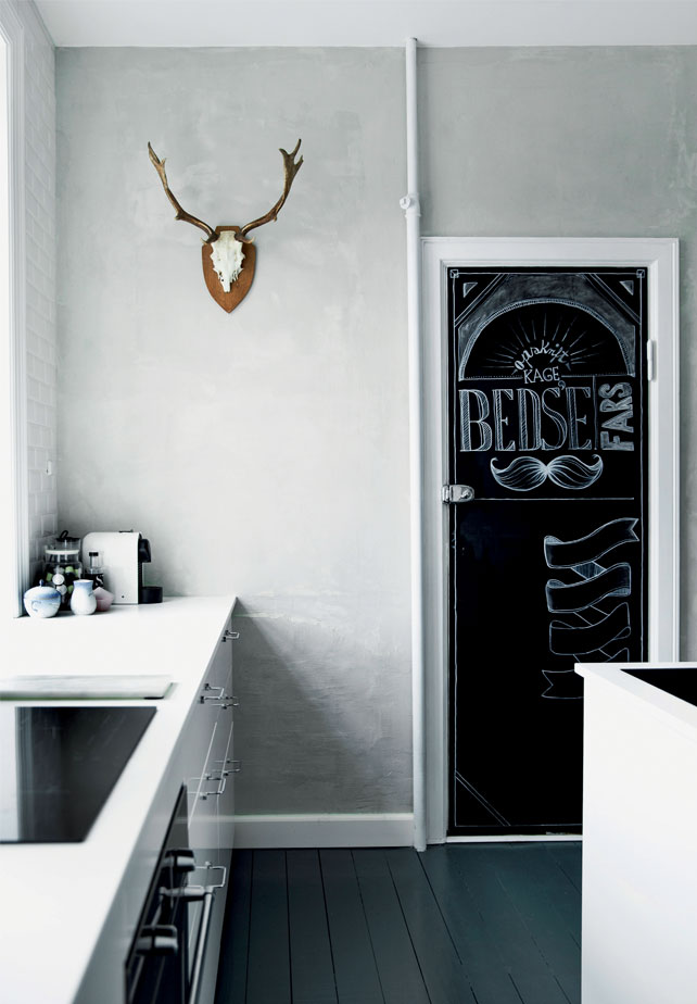 A chalkboard door makes the kitchen more relaxed and let you not take the monochrome interior too seriously