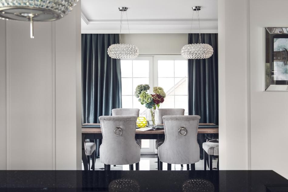 The dining space continues the decor theme with rhienstone lamps and chic upholstered chairs
