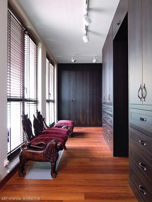The dressing room has a lot of black oak wardrobes with leather pulls