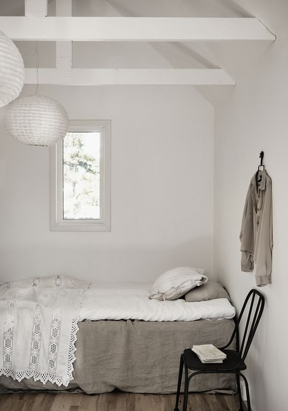 The guest bedroom is all-white, only the floors are wooden