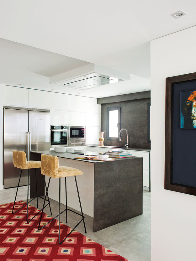 The kitchen is rather small, kept in white and grey - stainless steel appliances and concrete cooking surfaces