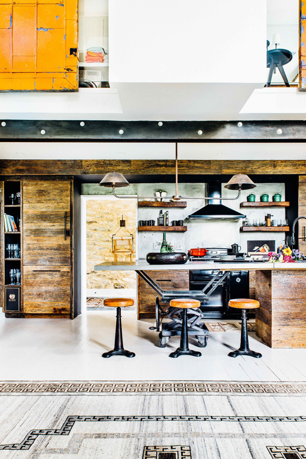 The kitchen is totally industrial, decorated with blackened steel and reclaimed wood
