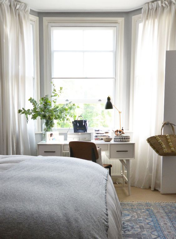 serene bedroom with a white desk by the window