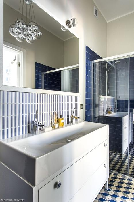 07 The bathroom is decorated in shades of blue, with 3D floor tiles and a bauble lamp