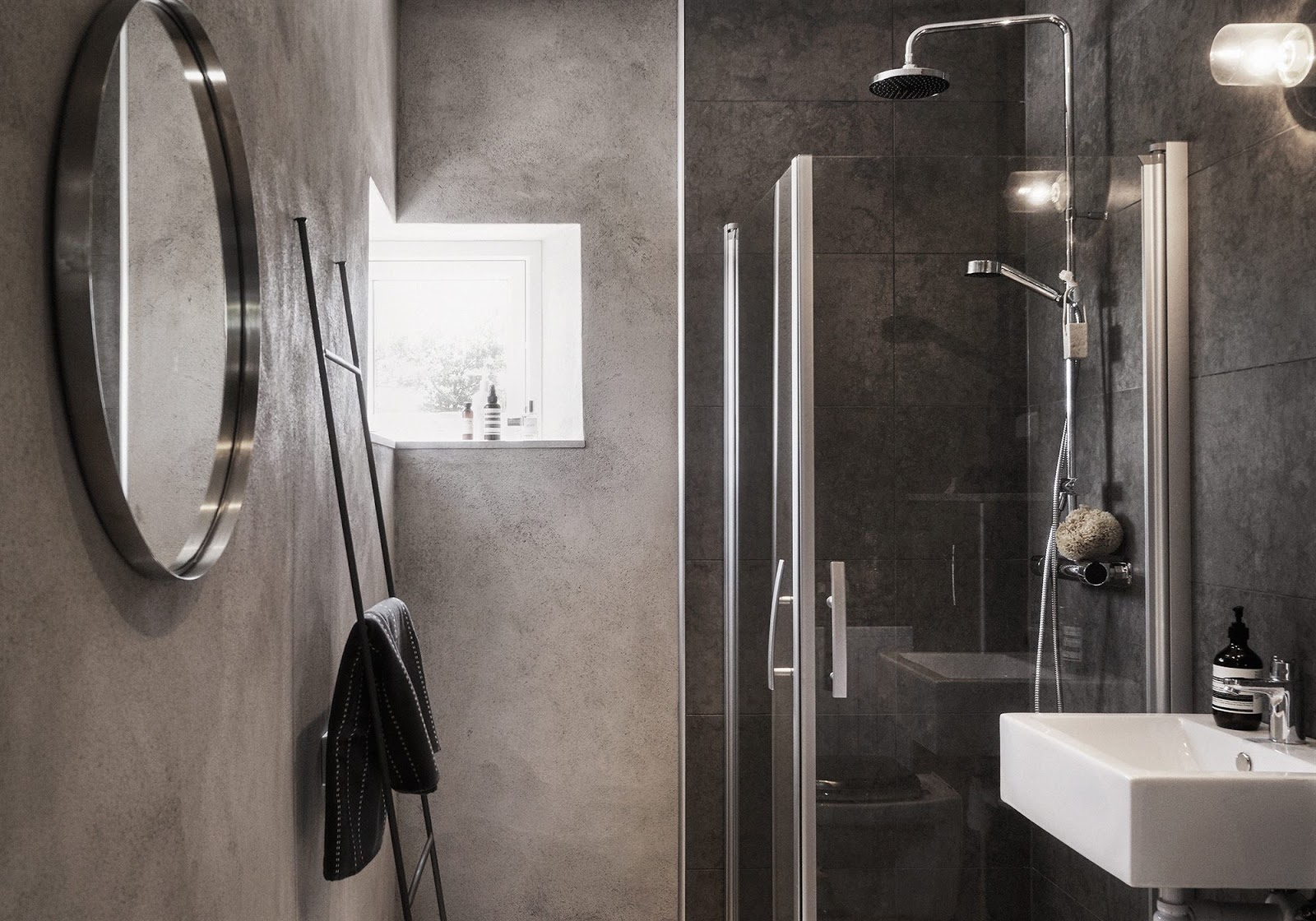 The bathroom is decorated with concrete and dark tiles that remind of concrete too