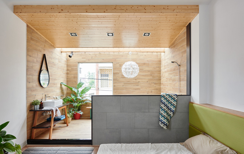 The bedroom opens into the timber-clad bathroom