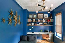 07 The home office is dazzlign blue with a cool lamp and a 3D wall art