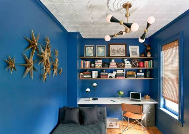 The home office is dazzlign blue with a cool lamp and a 3D wall art