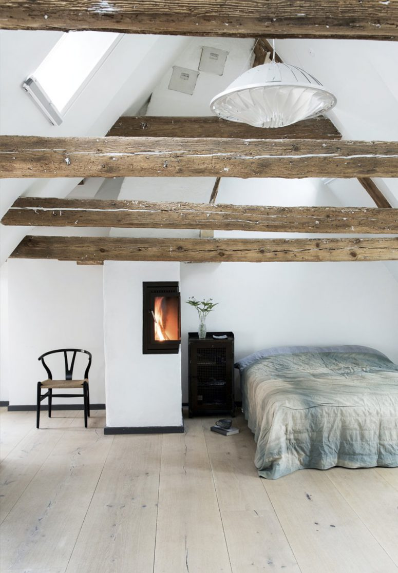 The master bedroom is an attic space with exposed wooden beams, a wood hearth and Dinesen oak floors, very peaceful and relaxing