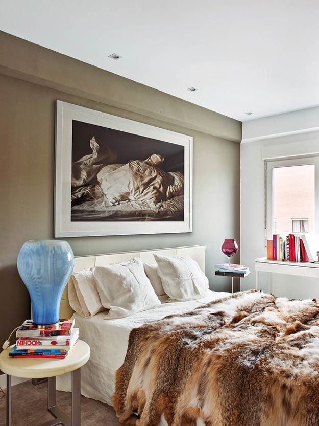 The bedroom is cozy with an olive accent wall and a gorgeous fur bedspread