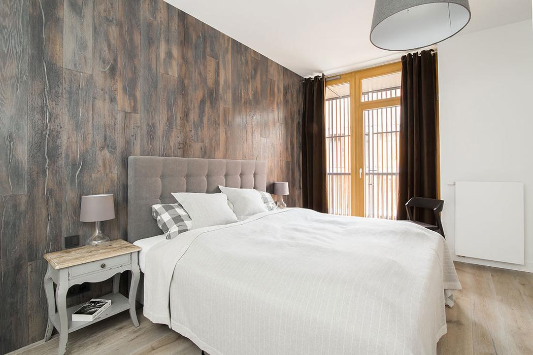 The master bedroom is covered with various types of wood to achieve a soothing ambience