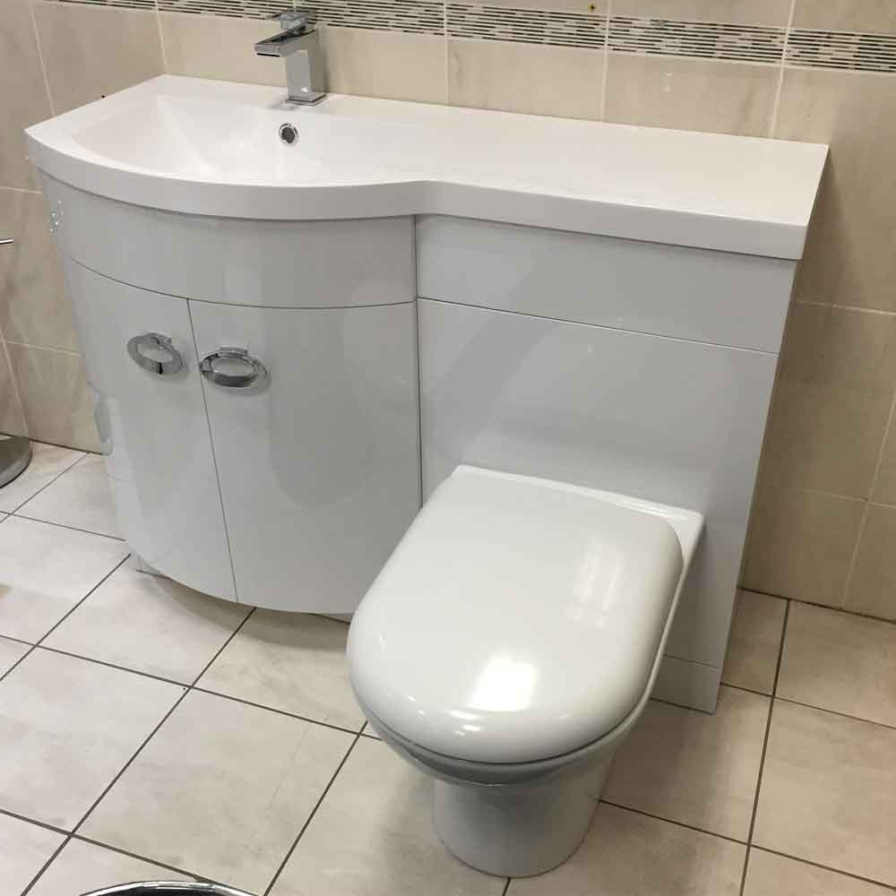 curvy sink with a countertop and a toilet