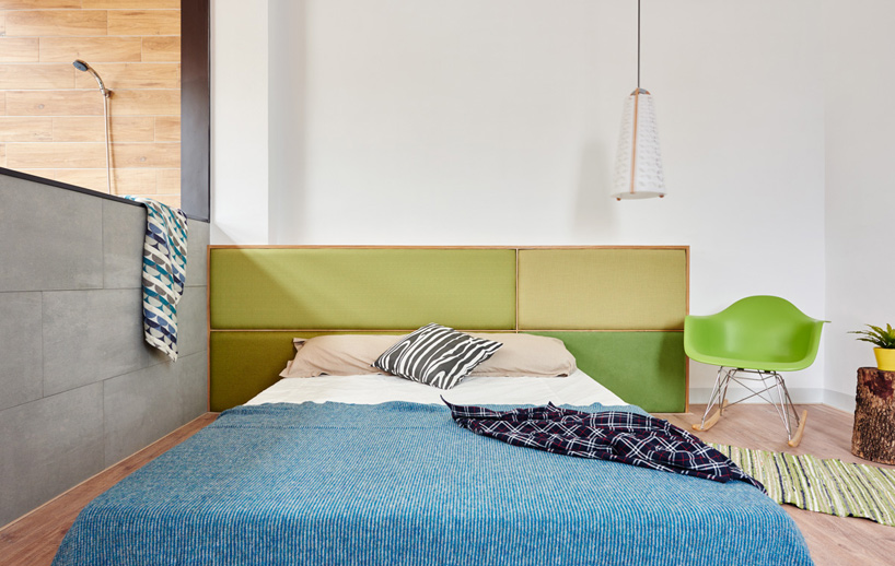 the master bedroom can boast of several bold touches like a green headboard and chair and a blue bedspread