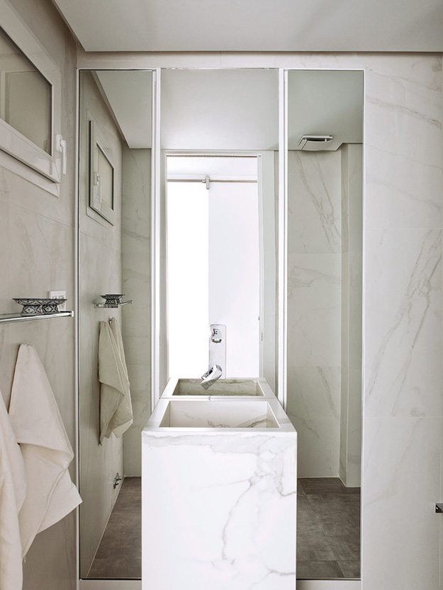 The bathroom is small and elegant, clad with white marble