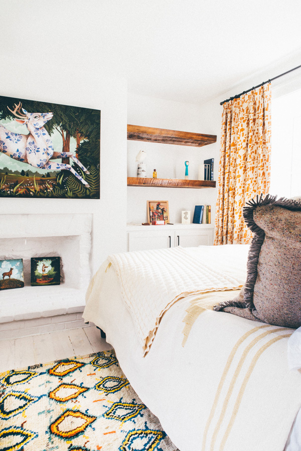 The second bedroom is decorated with warm-colored textiles and animal artwork
