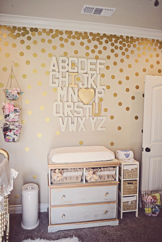 white and gold changing table with a cool alphabet art over it